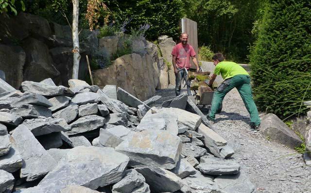 Zwei Männer verladen Natursteine für Peter Bergs Trockenmauerworkshop.