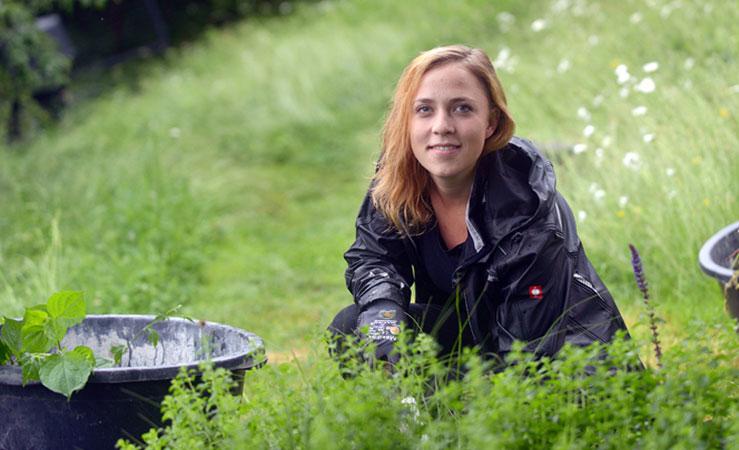 Anna Kuptz als Projektplanerin auch im Garten tätig und schneidet Pflanzen