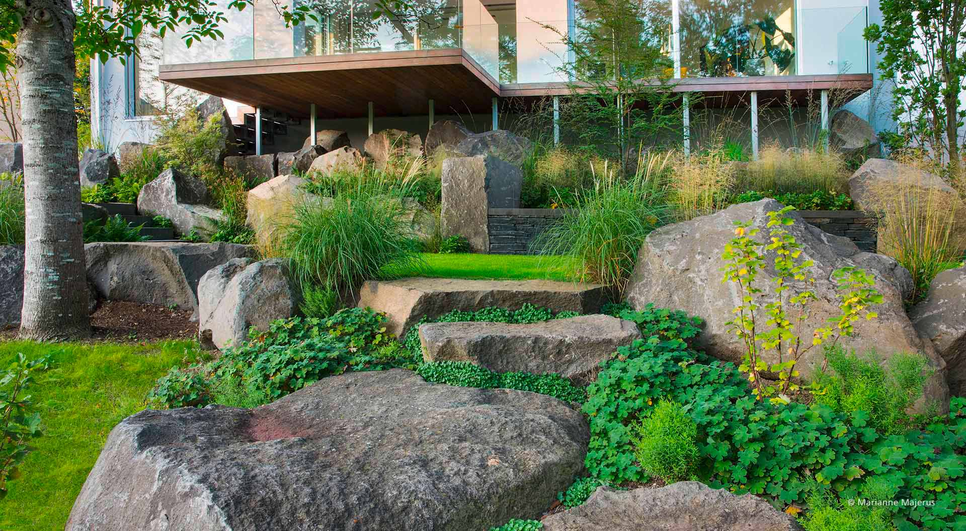 Many plants and stones under a balcony stilt foundation
