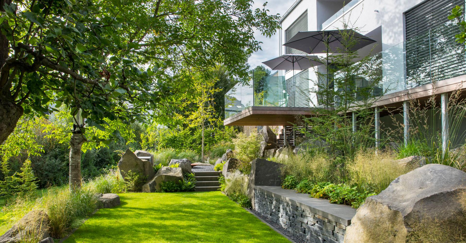 Moderner Garten mit Hochbeeten, gepflegtem Rasen und großem Balkon