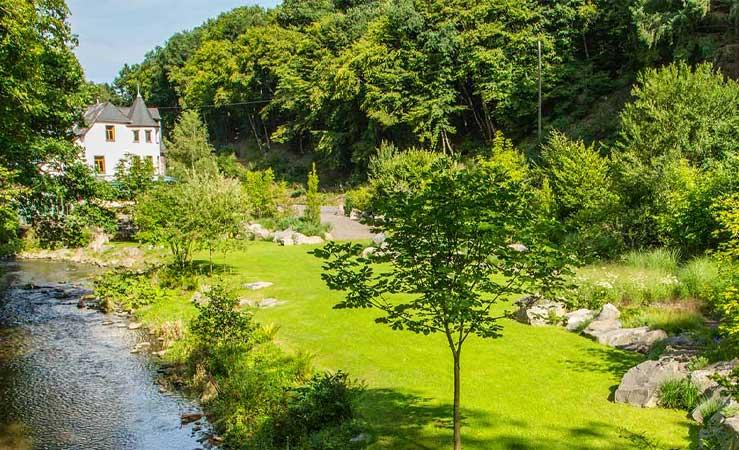 Dieser Firmengarten verfügt über eine weitläufige Grünfläche und einen Wasserlauf