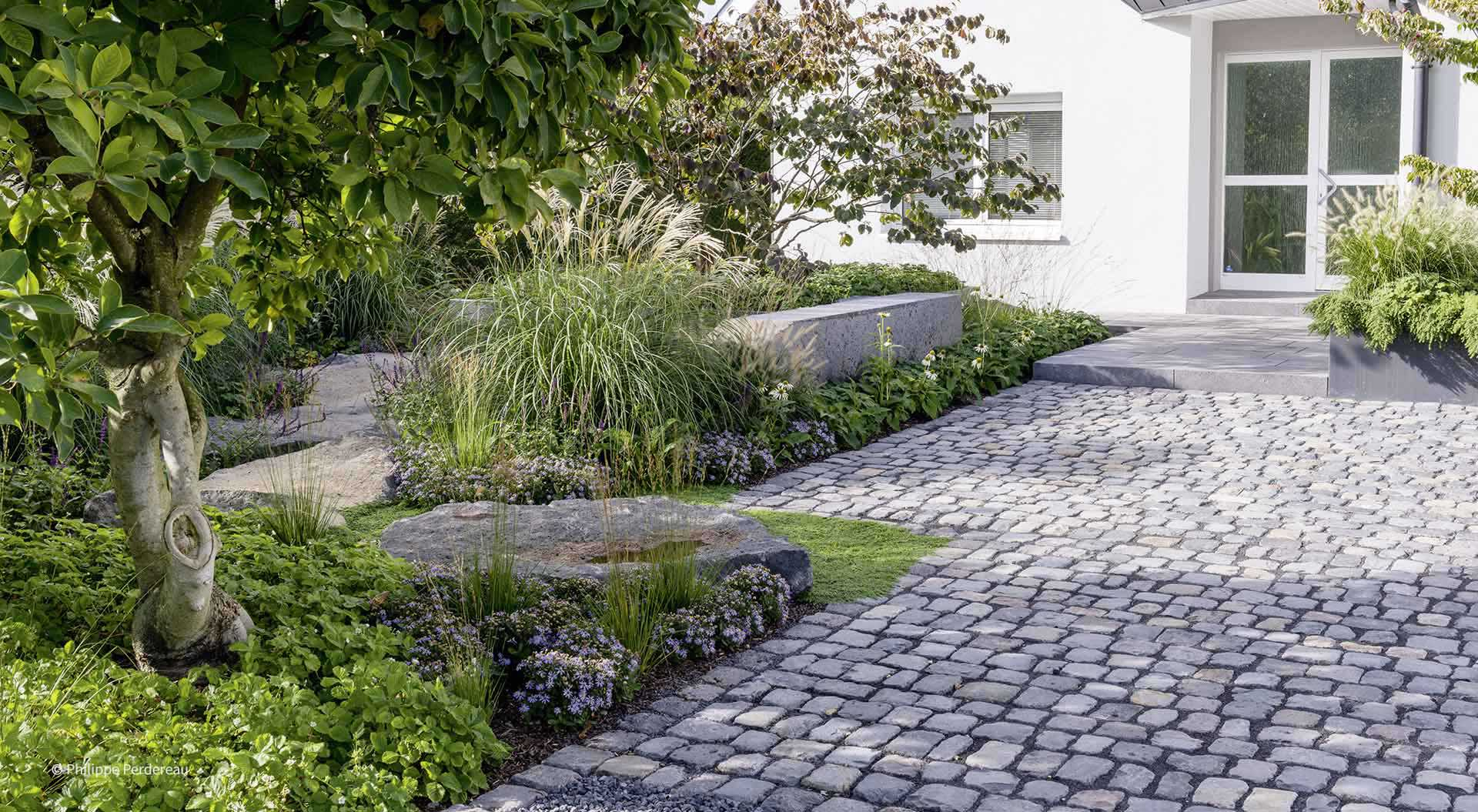 Cobblestone driveway adjoins natural front garden