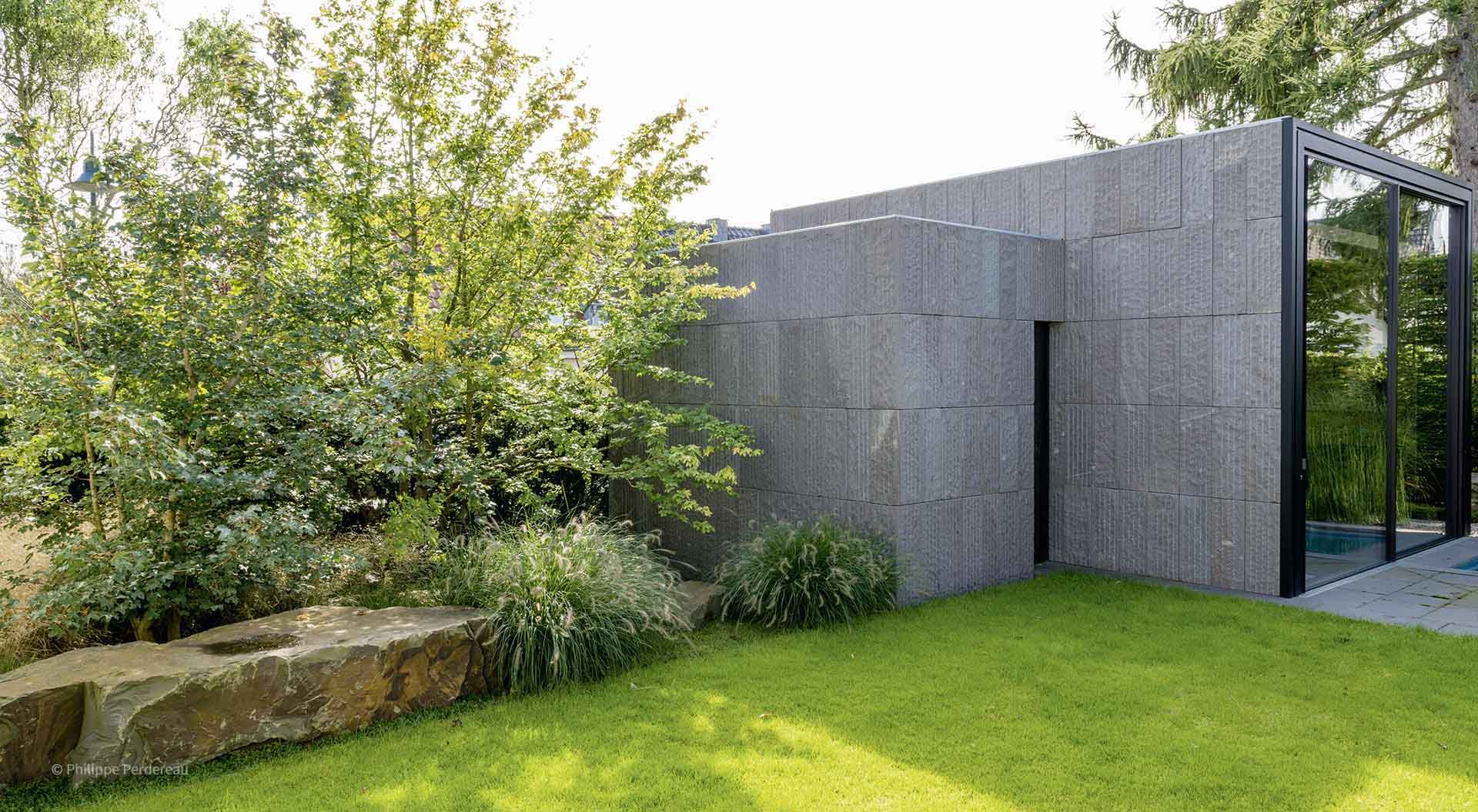 Natural stones and plants adjoin the grass and a lean-to