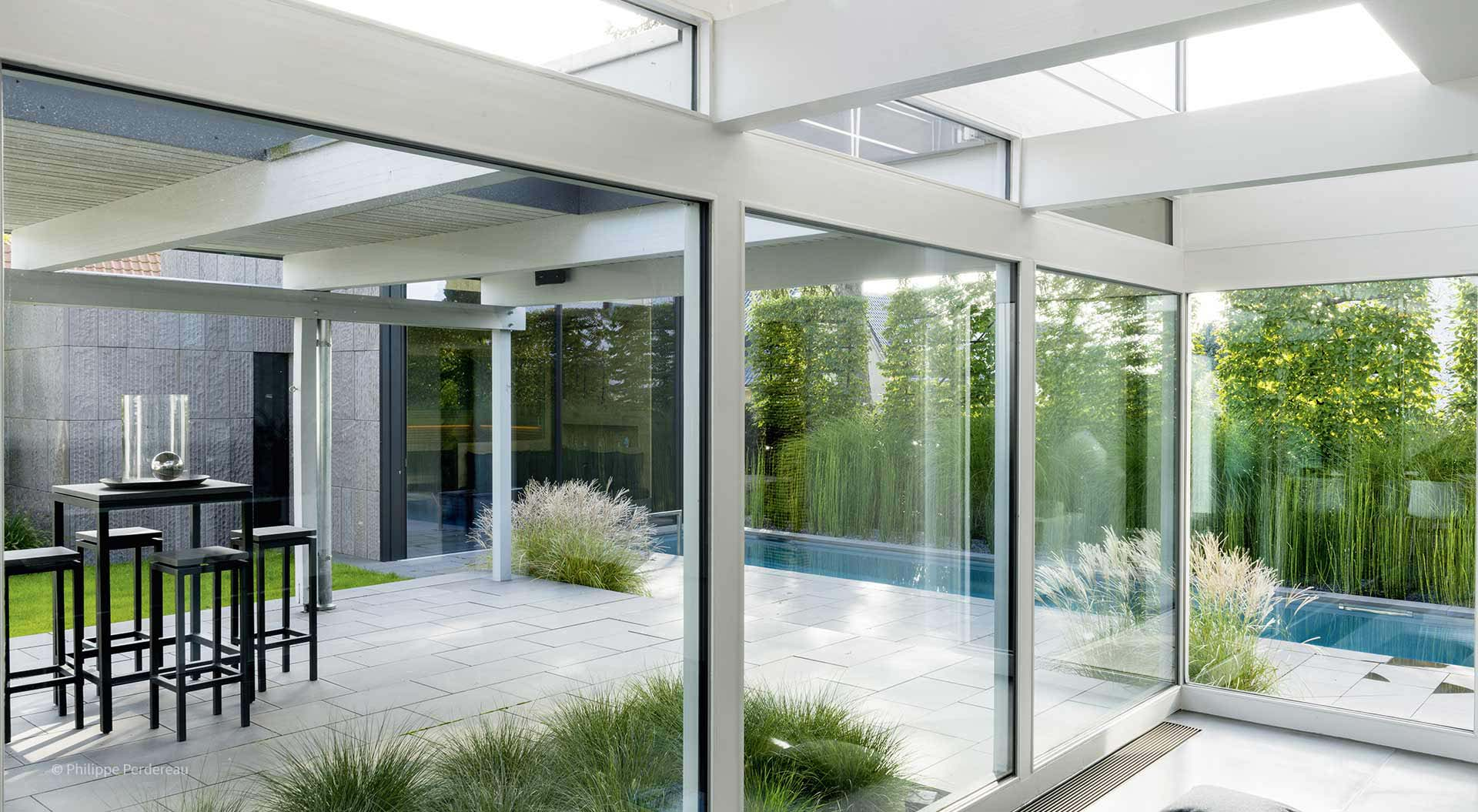 Modern patio with conservatory in front of the small garden with pool