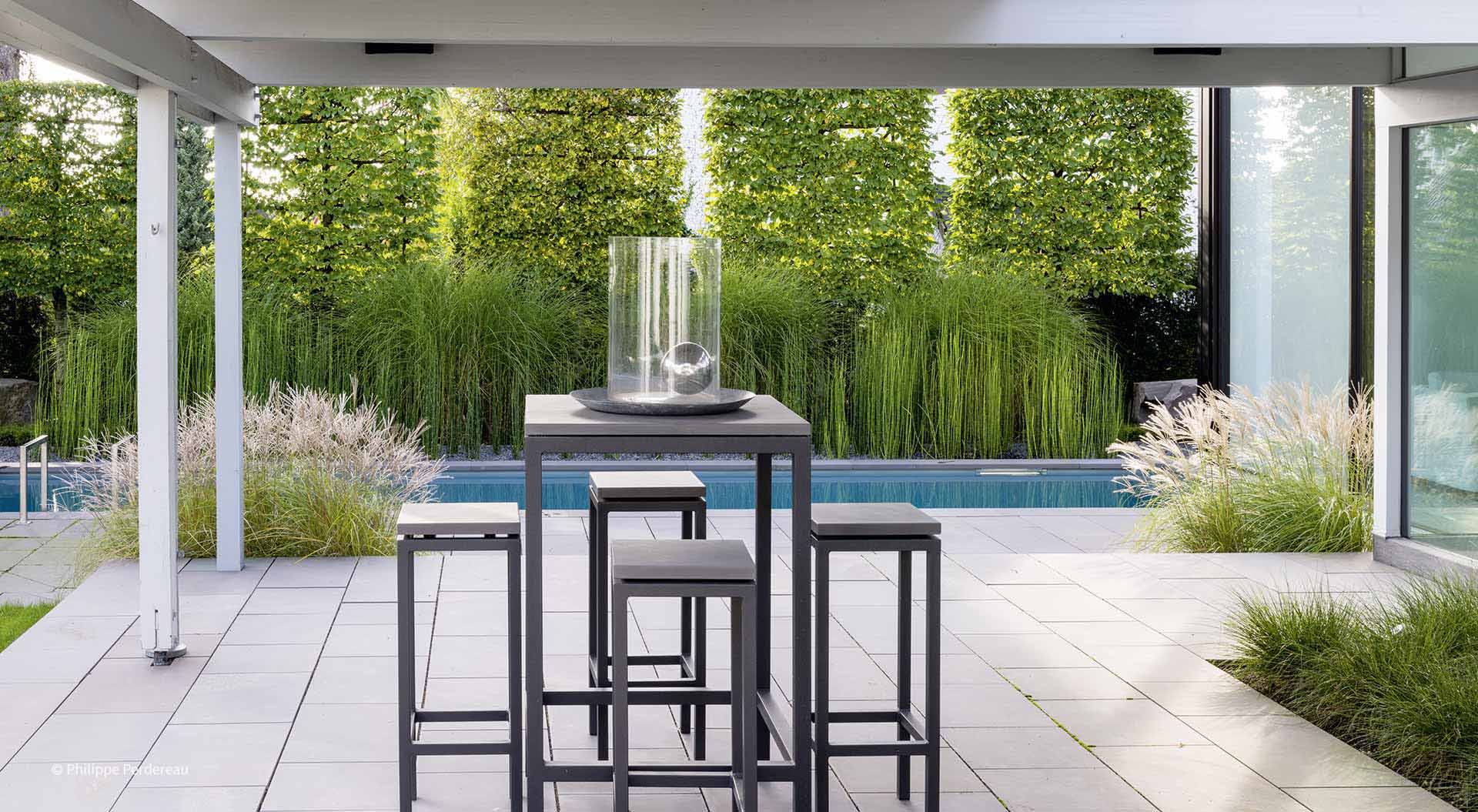 Big bright patio with a small pool and many grasses