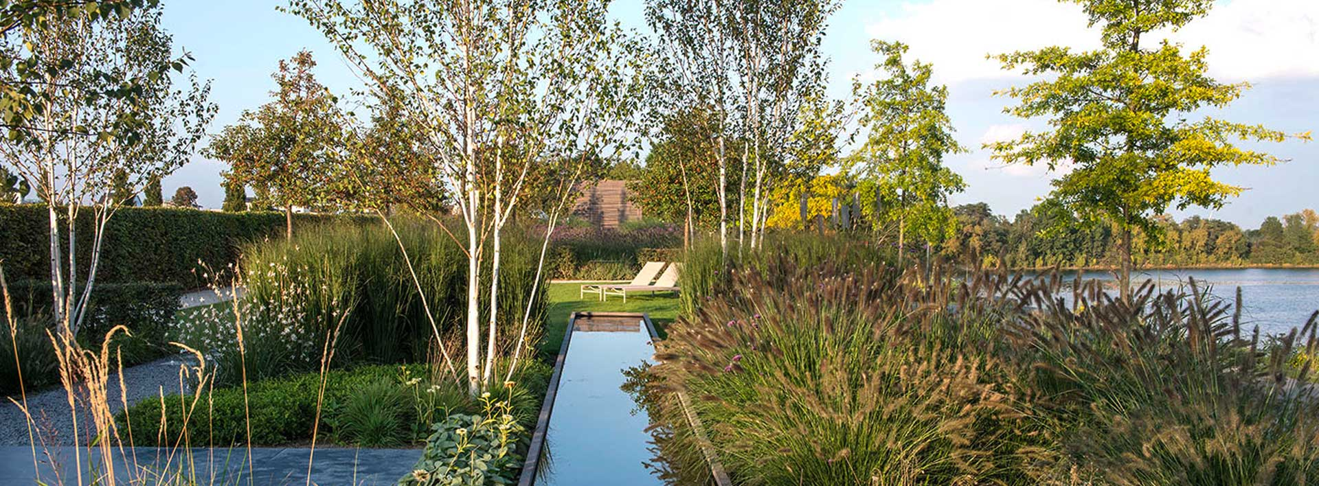 Show garden nearby a lake that contains grasses, a pond, cravel ground and trees
