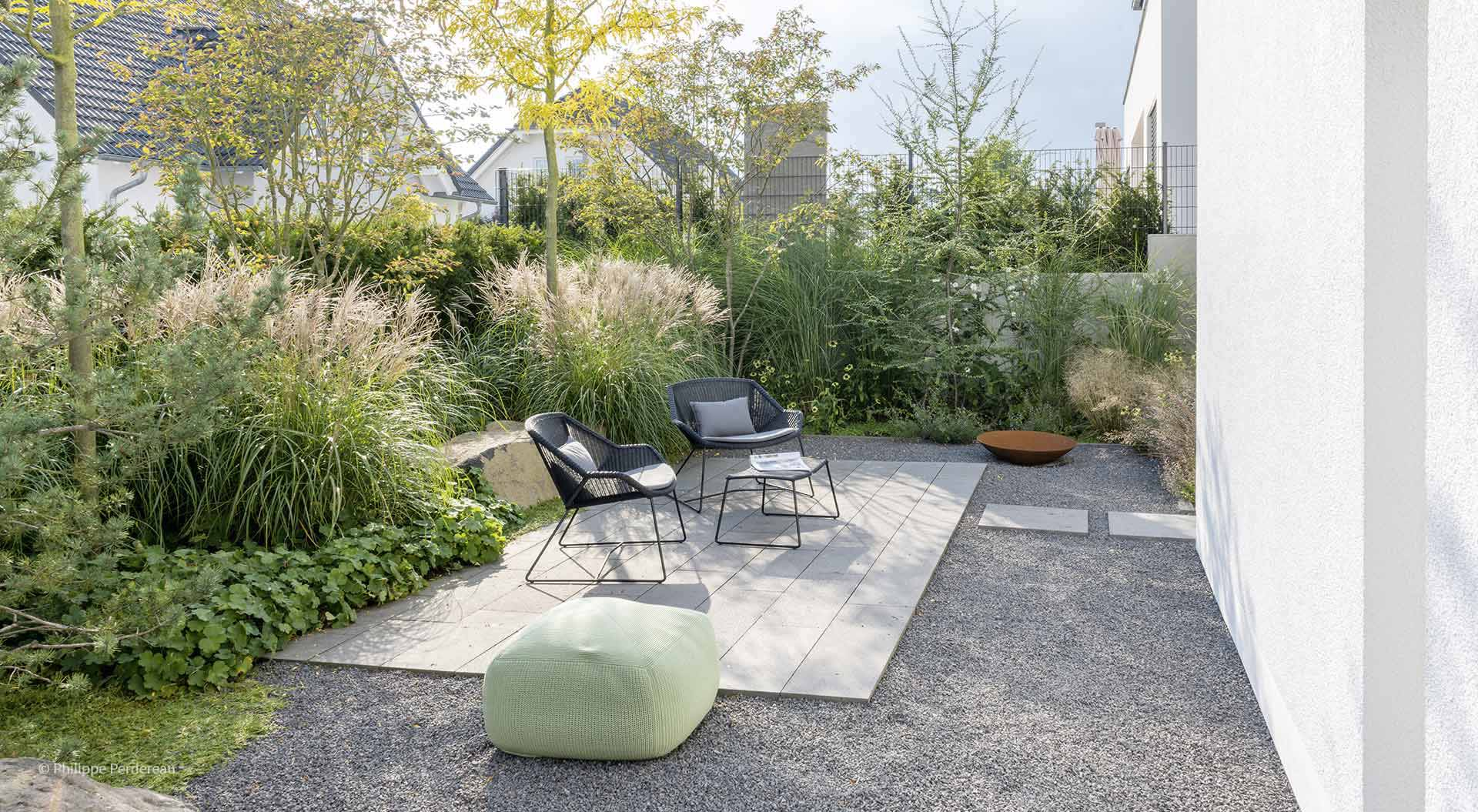 Plates that form a patio on a gravel floor in front of plants