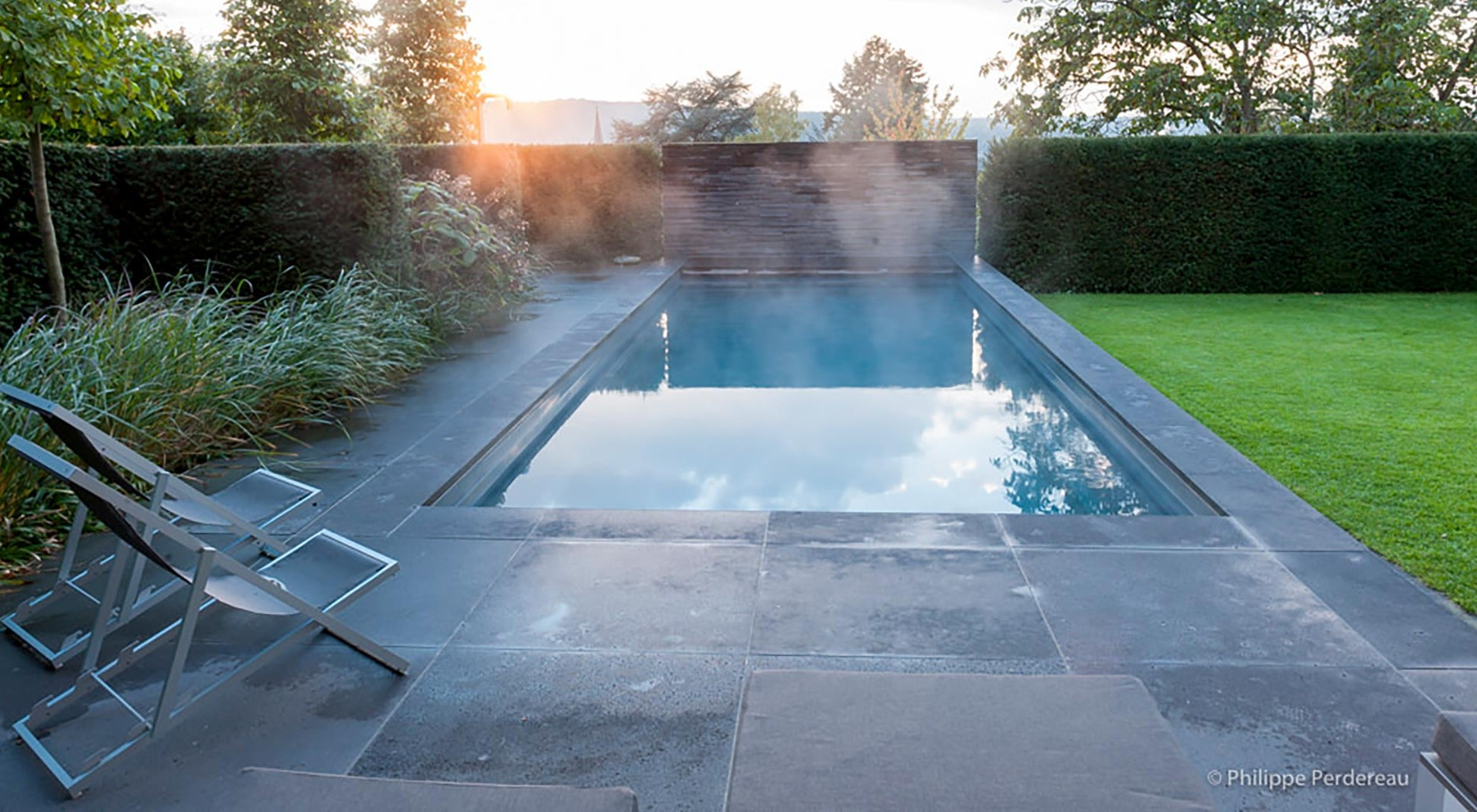 Garden with steaming pool on stone patio in parallel to grass