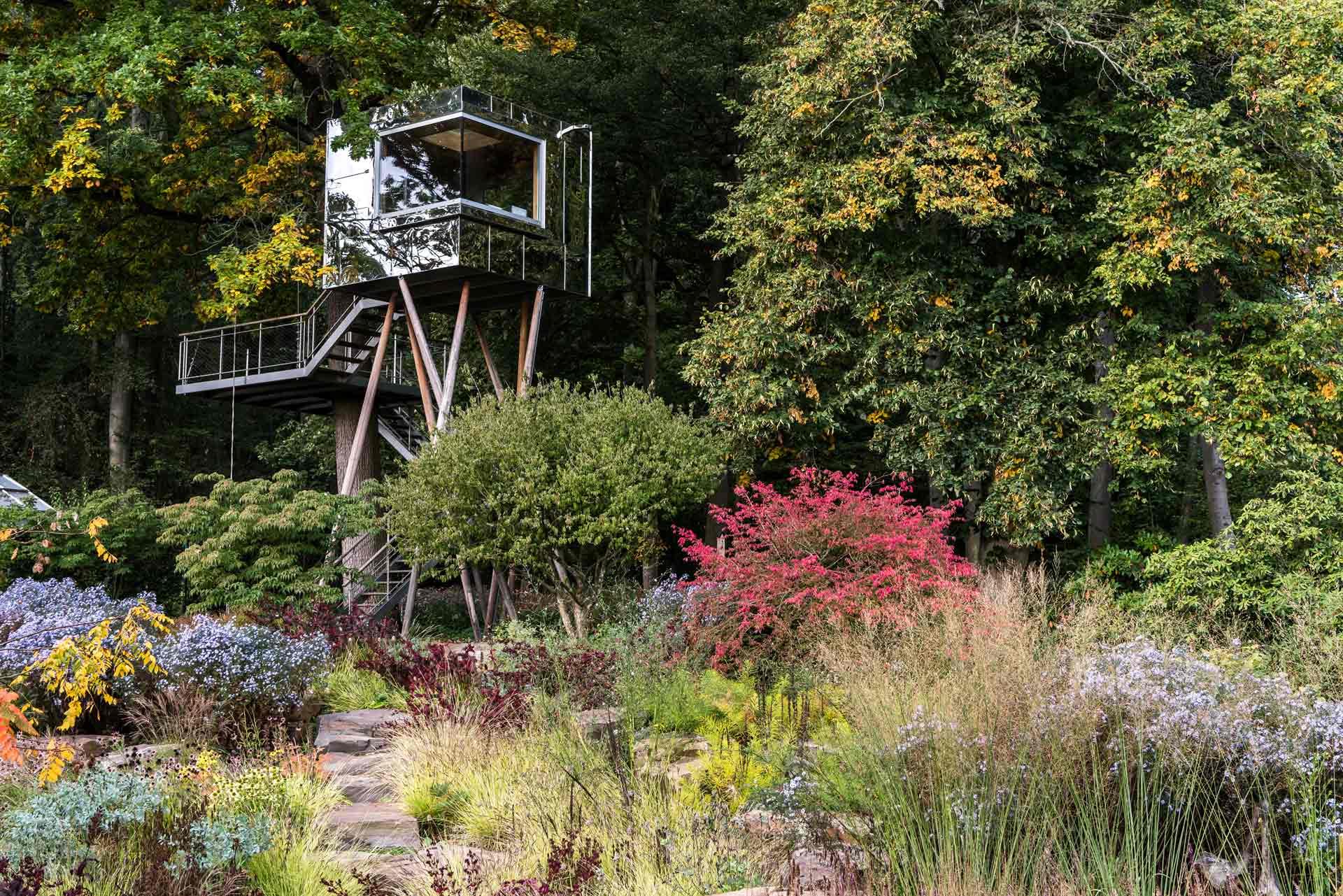 Gläsernes Gartenhaus in vielfältigem Naturgarten