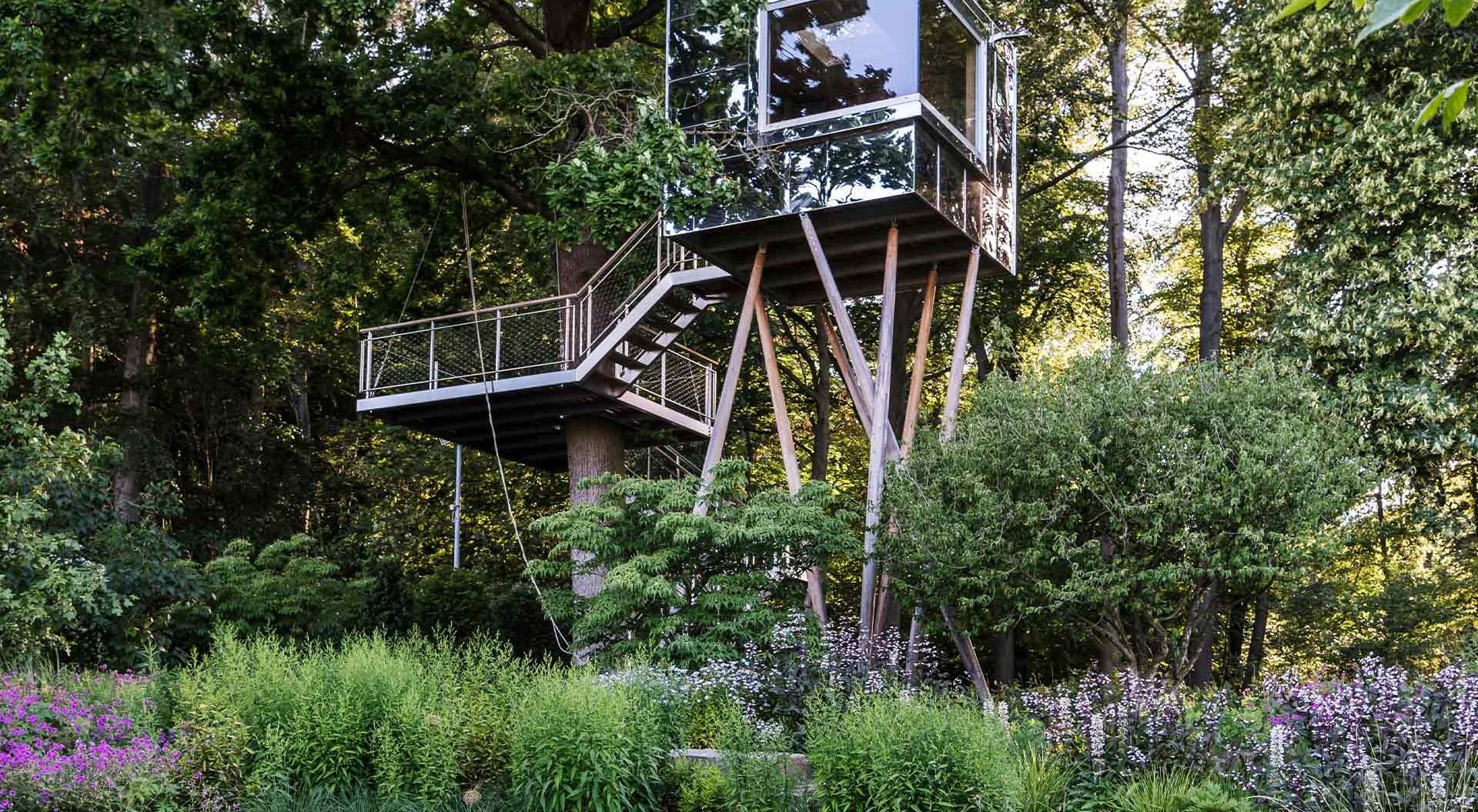 Modernes gläsernes Baumhaus zwischen Bäumen, Blumen und Sträuchern
