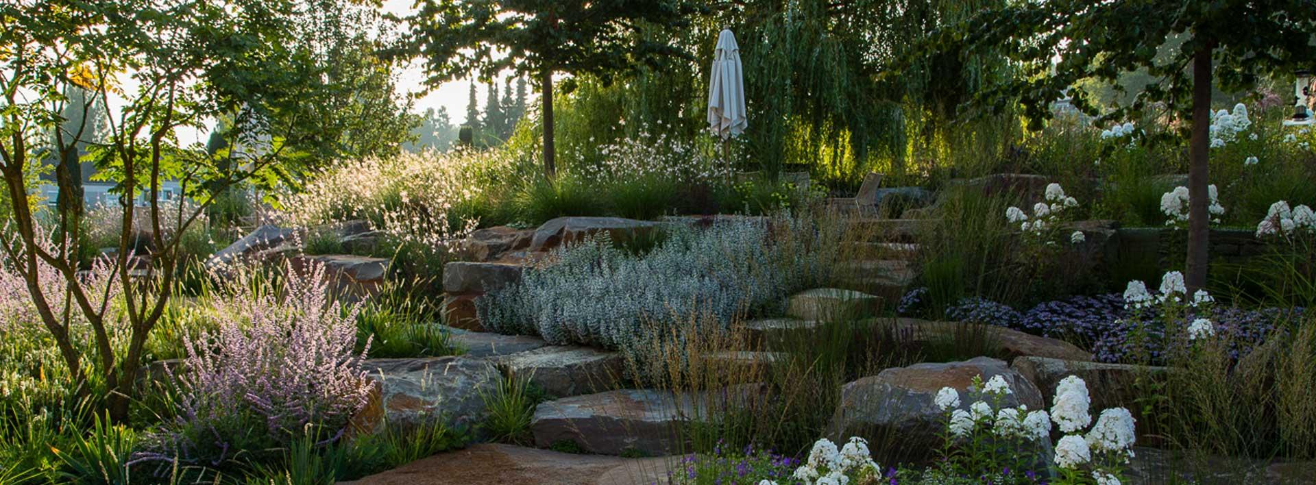Vielfältiger Garten mit vielen Steinen, Treppen, Blumen und Pflanzen