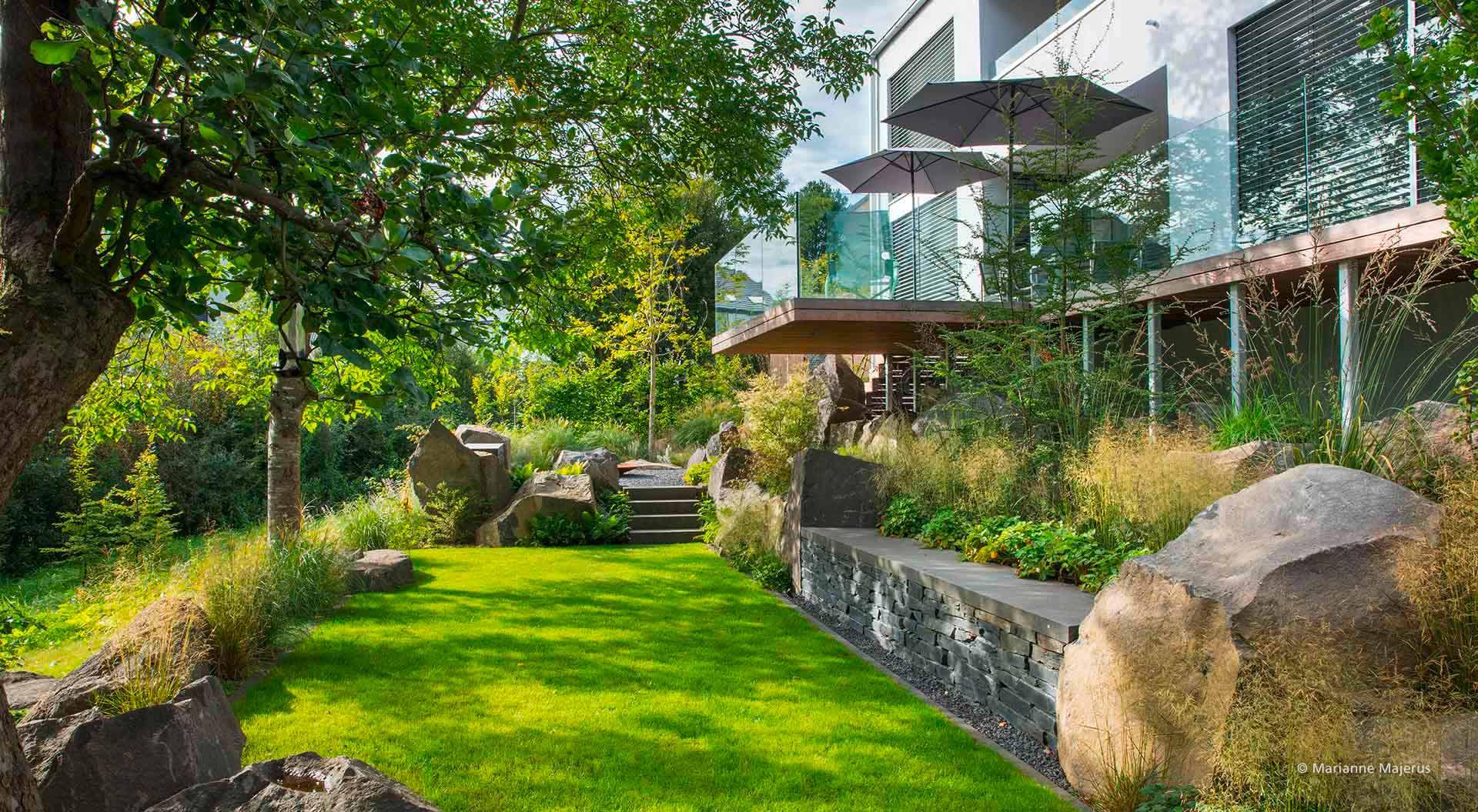 Moderner Garten mit Glasfront und Balkon