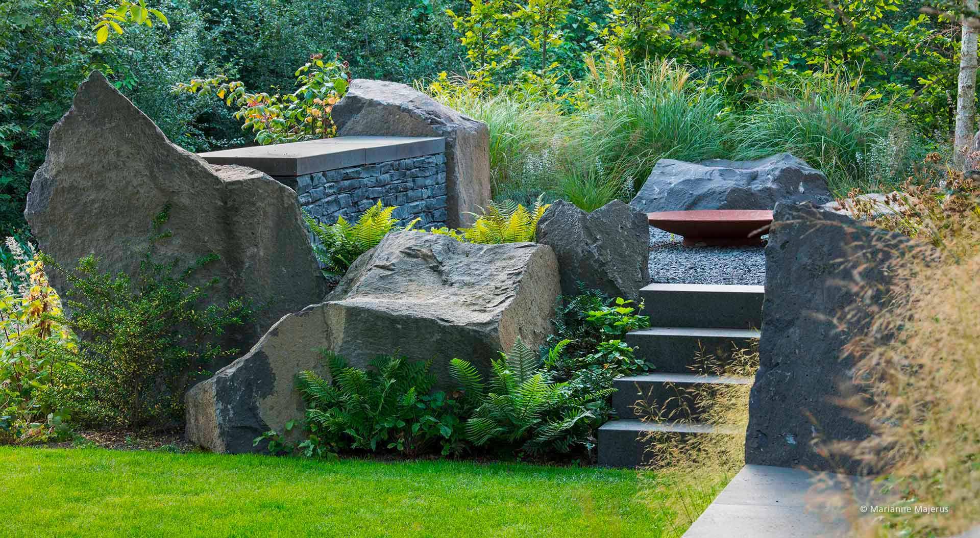Treppe führt von Rasen hoch zu Steinlichtung im Hanggarten