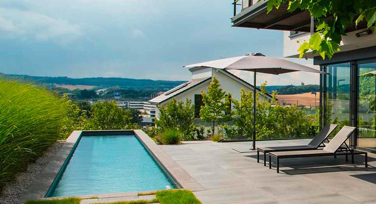 Betonierte Terrasse mit Pool und Blick in die Ferne