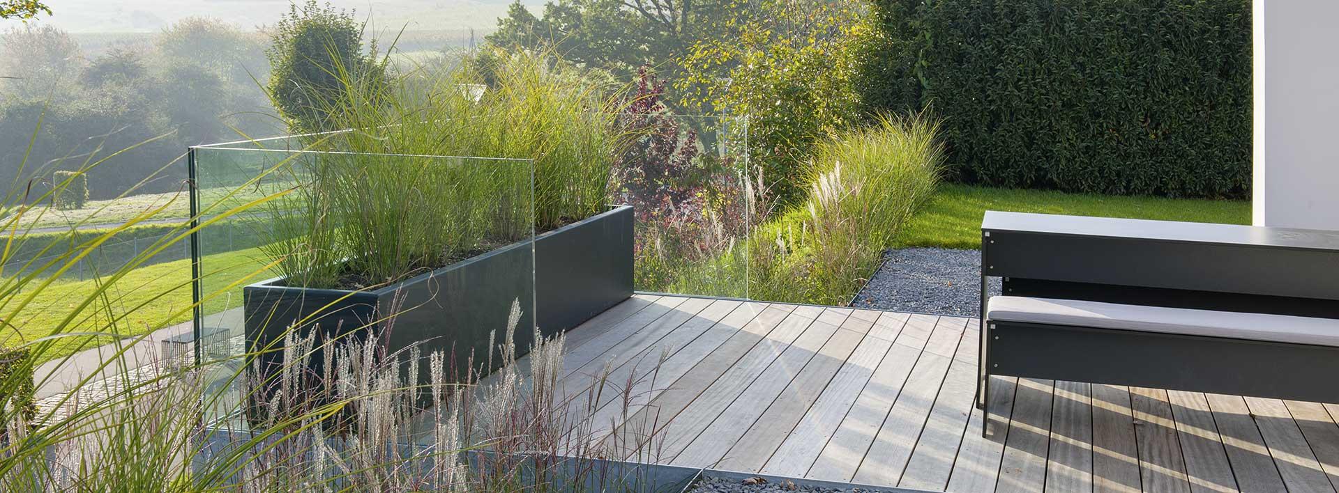 Bild einer modernen Terrasse mit Holzbalken vor frischem Garten