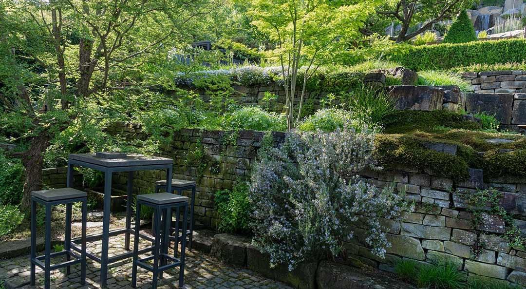 Natursteinmauer-Terrassen an schattiger Sitzgelegenheit