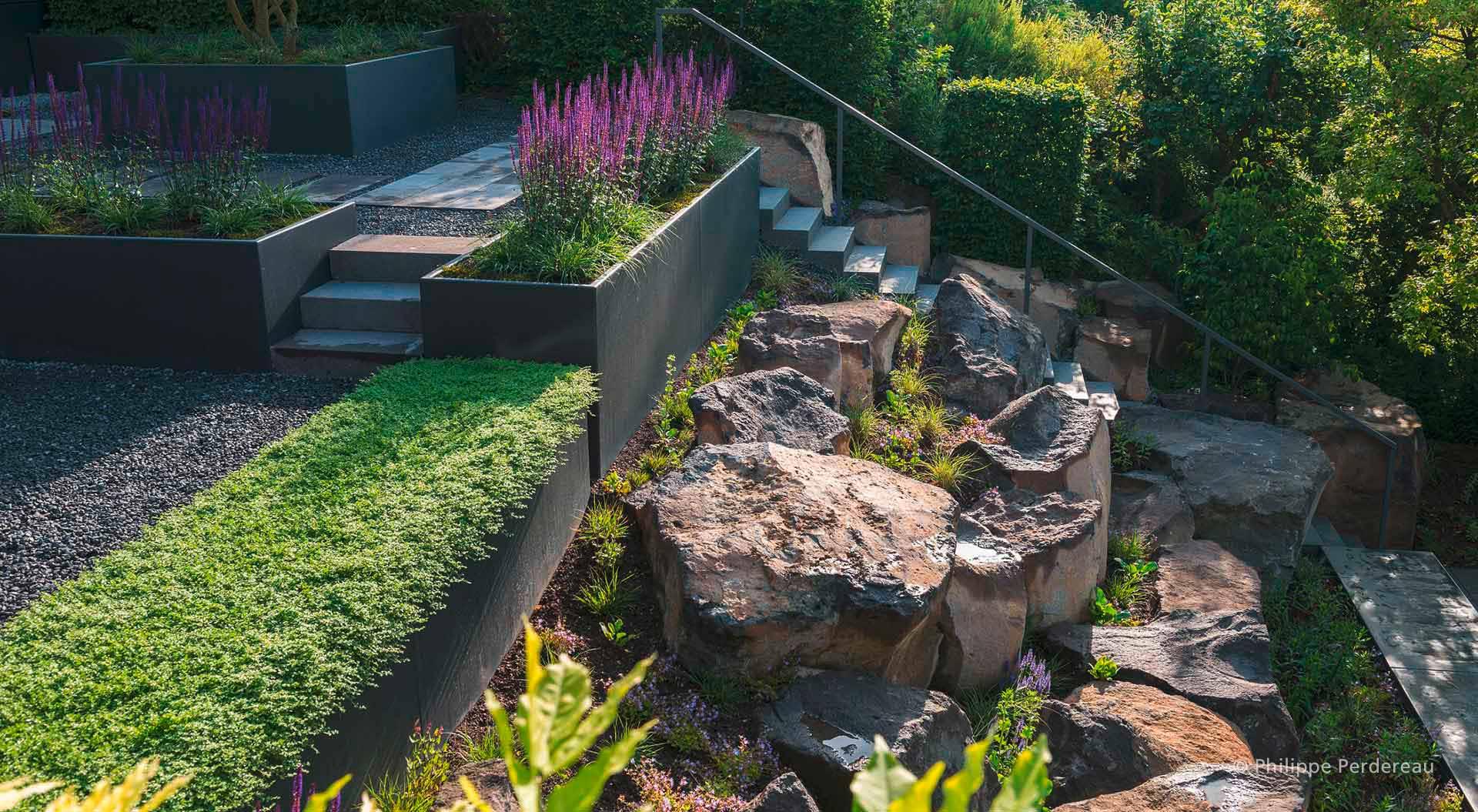 Treppe im Hanggarten führt zwischen Steinen hinauf zur nächsten Ebene