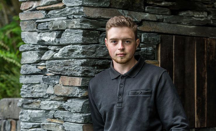 Gartenbauer Phillip Schimek vor Natursteinmauer