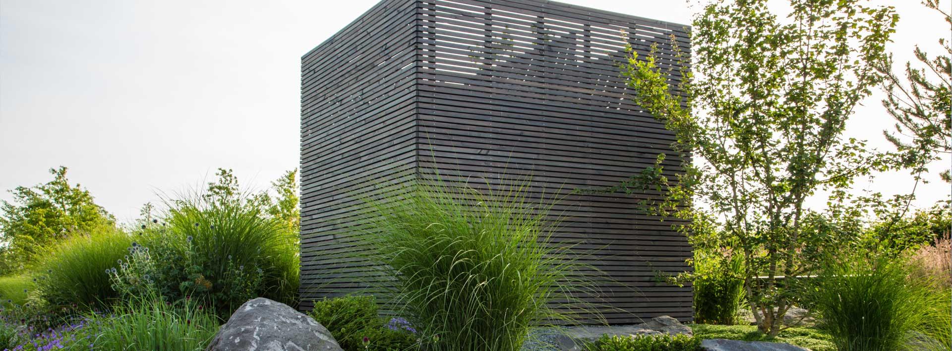 Gartenhaus aus Holz mit Gräsern und Naturstein