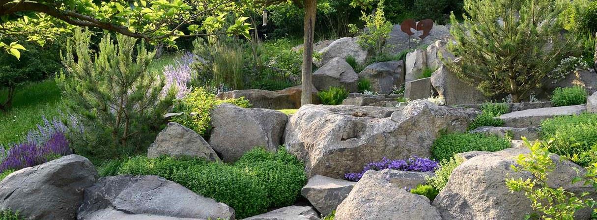 Dieser Hanggarten wurde mit Natursteinen angelegt und mit Bäumen, Sträuchern und Blumen bepflanzt