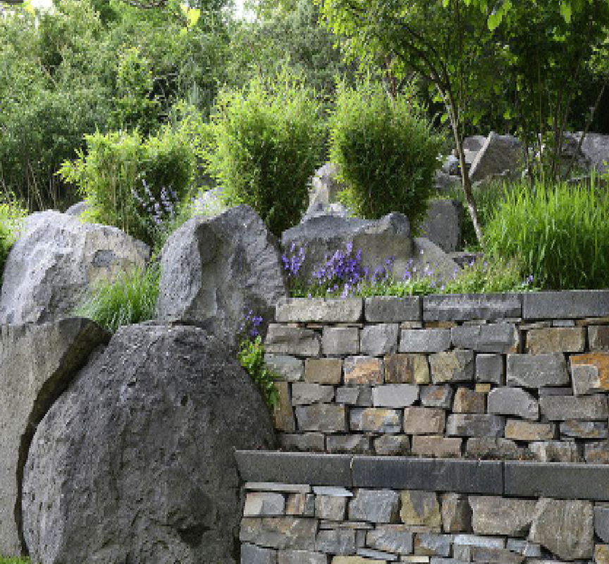 Blick auf von Peter Berg designtem Hanggarten mit Steinen und Pflanzen