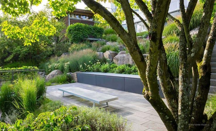 Hanggarten mit Baumbepflanzung und Sitzgelegenheit