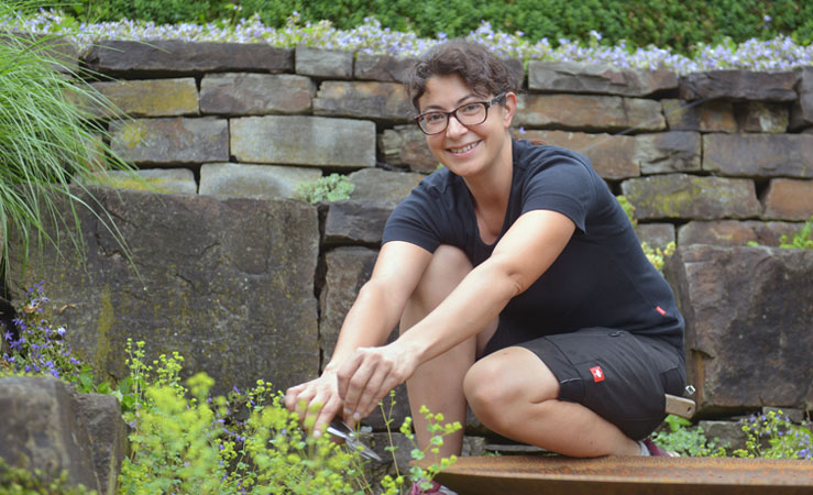 Katrin Mies als Gartenbauerin in Aktion auf Mauer beim Pflanzenbeschneiden