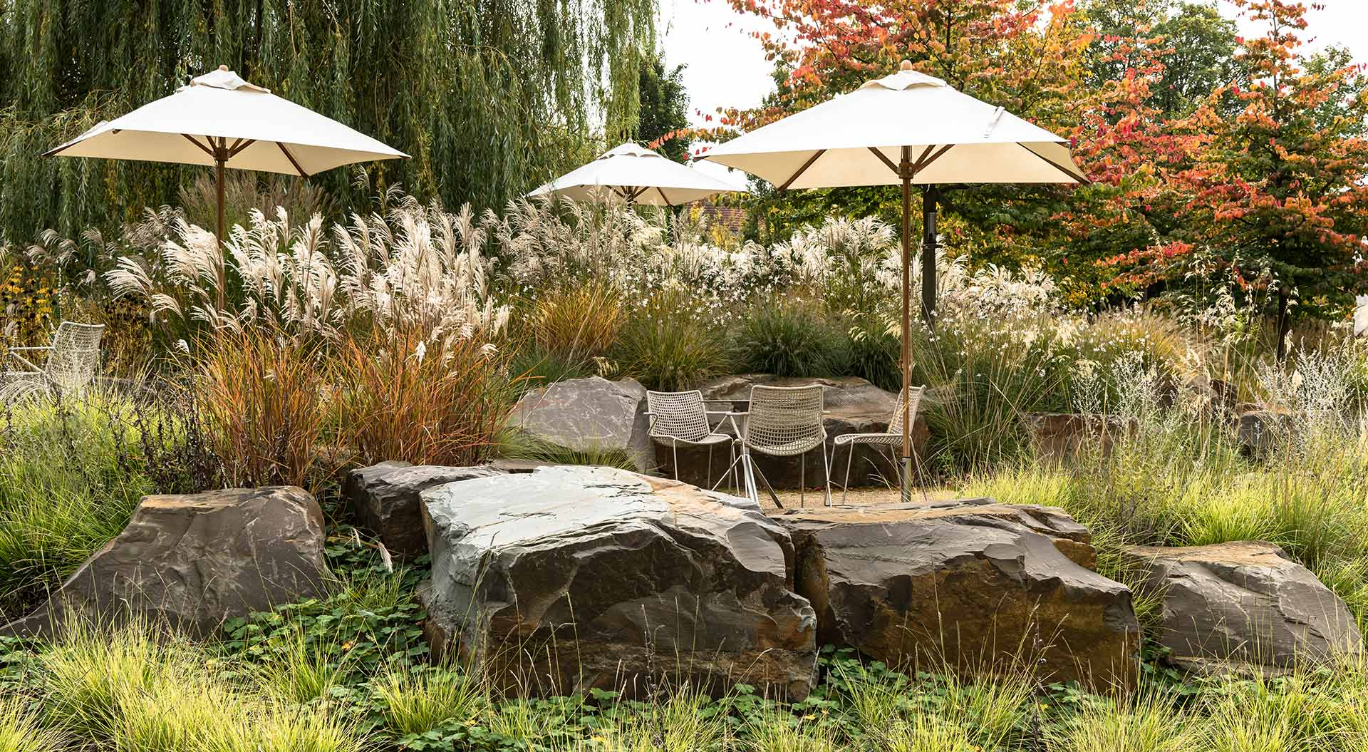 Natural stones surround a gravel terrace with chairs and parasols