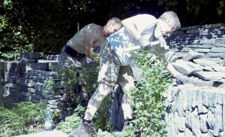 Zwei Mitarbeiter sind in Aktion und helfen bei Aufbau eines Gartens