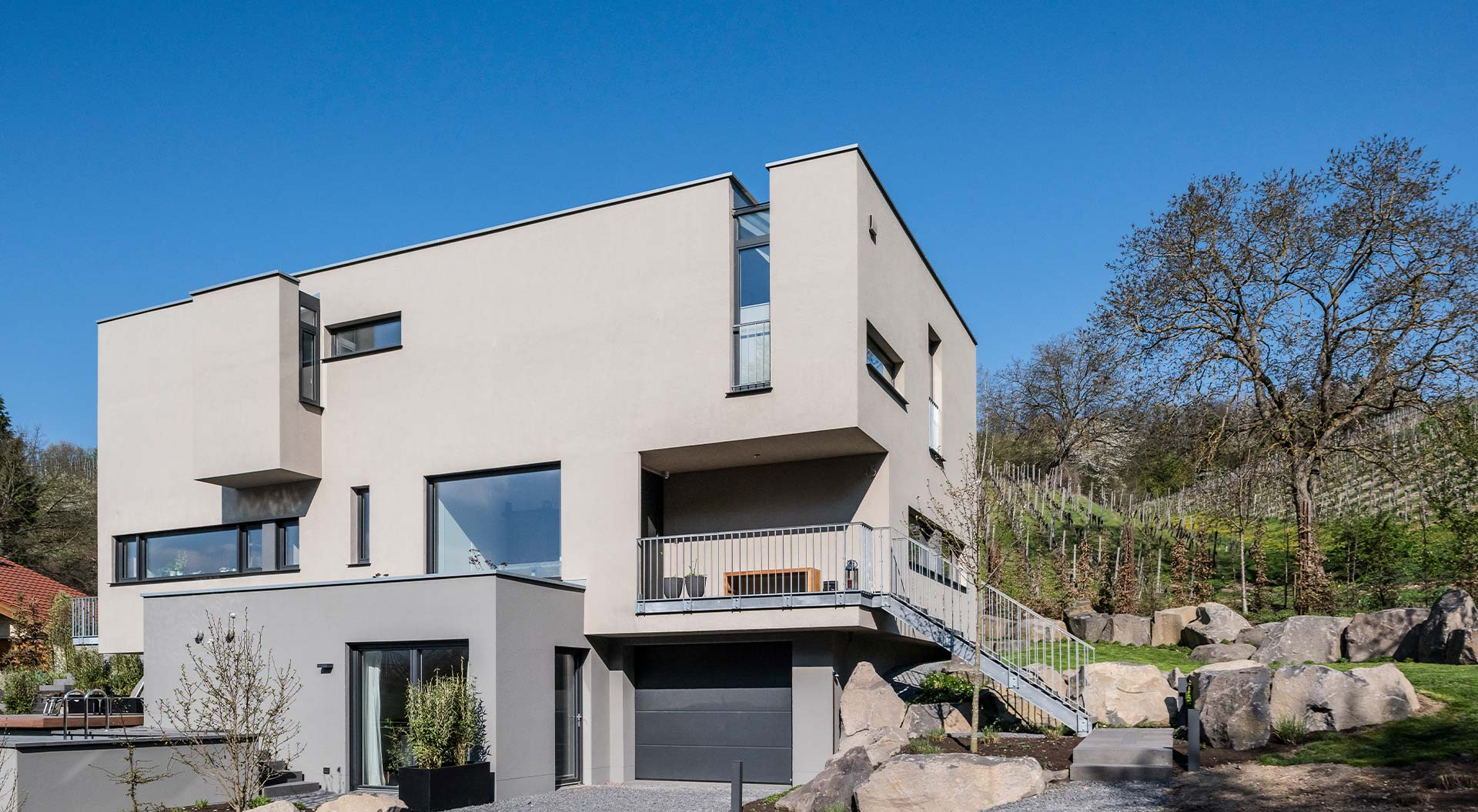 Modern house in block optics stands optimally at the slope and rounds the garden off