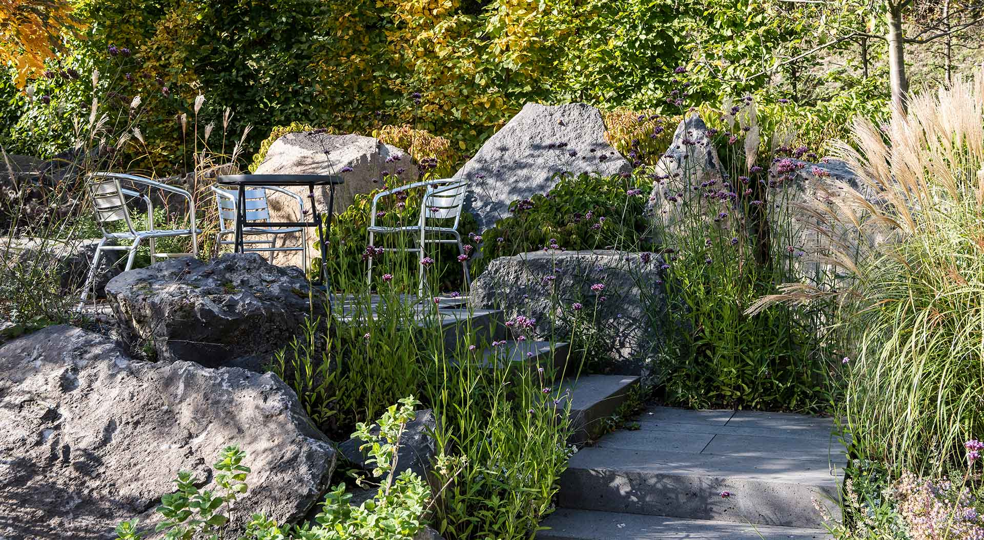Seating area between beautiful natural stones to which a staircase leads