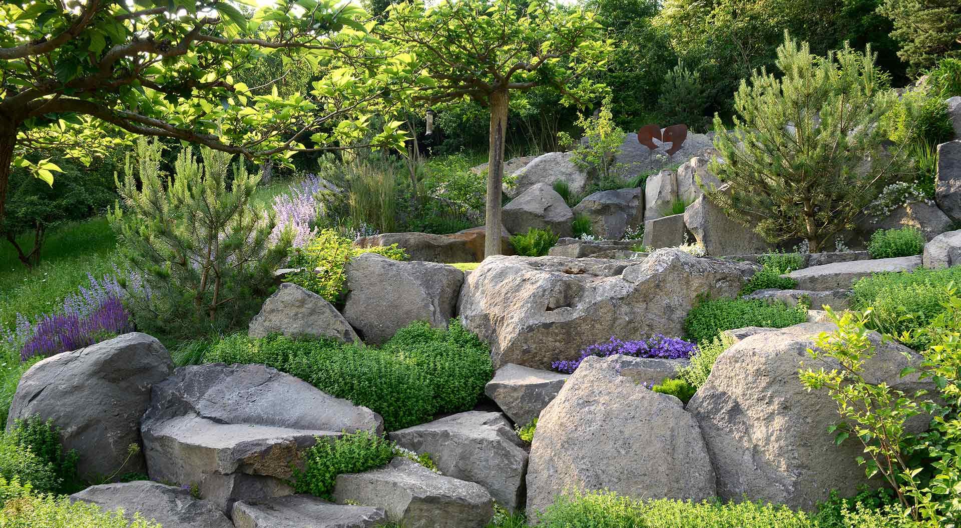 Hanggarten mit vielen Pflanzen und großen Natursteinen