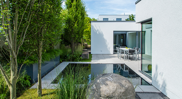Private garden with modern patio, pond and plants