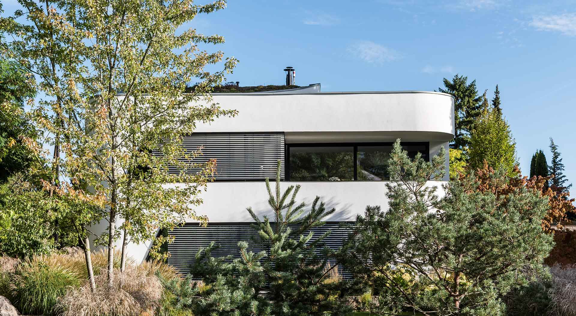 Coniferous and deciduous trees underline the beautiful appearance of the house