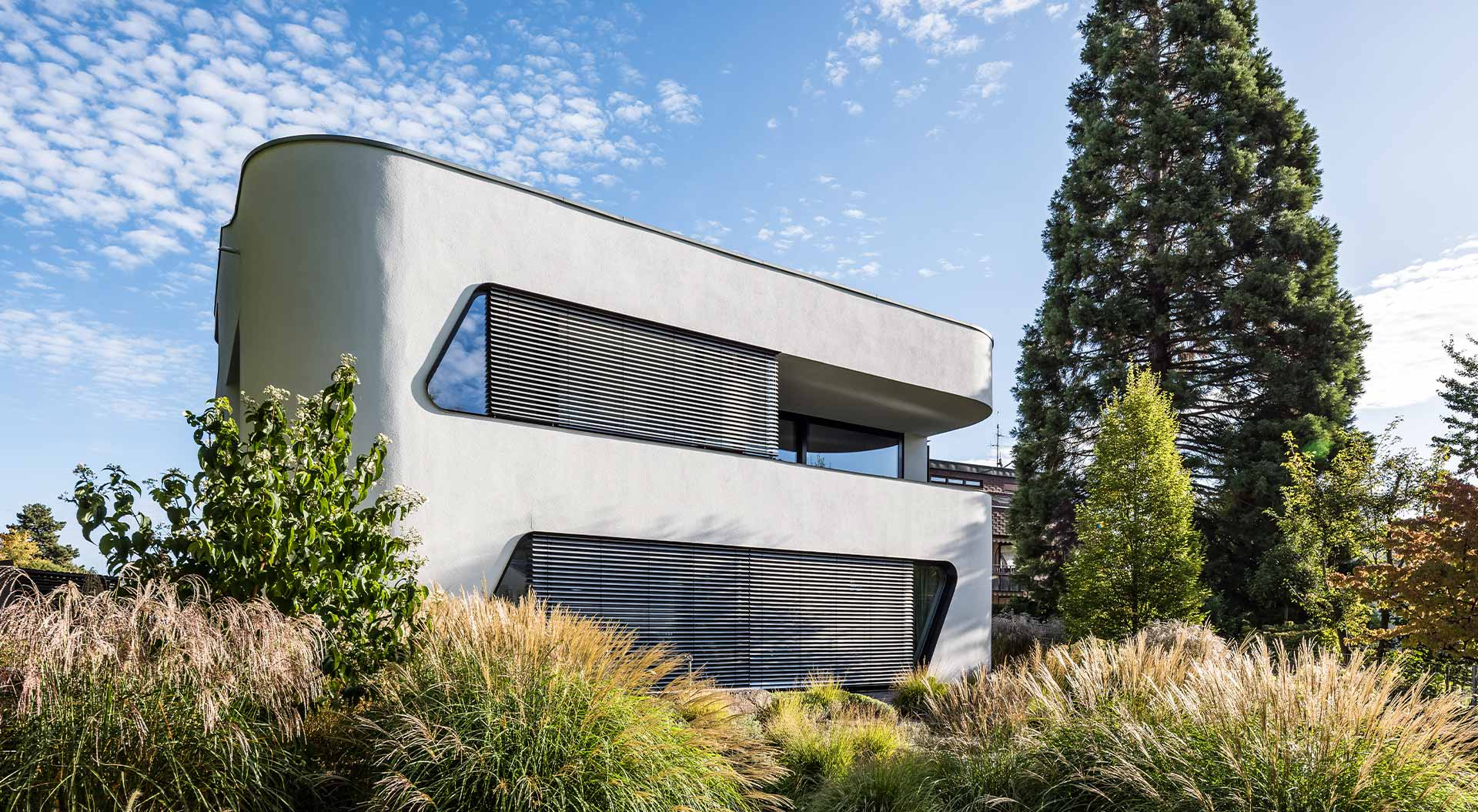 Modern residential house blends under a blue sky into the surroundings of plants and trees