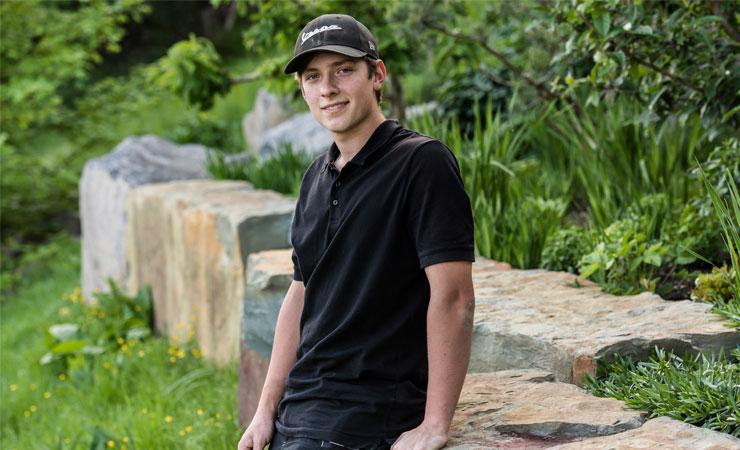 Azubi Fabian Brauchardt sitzt auf Natursteinmauer in grünem Garten