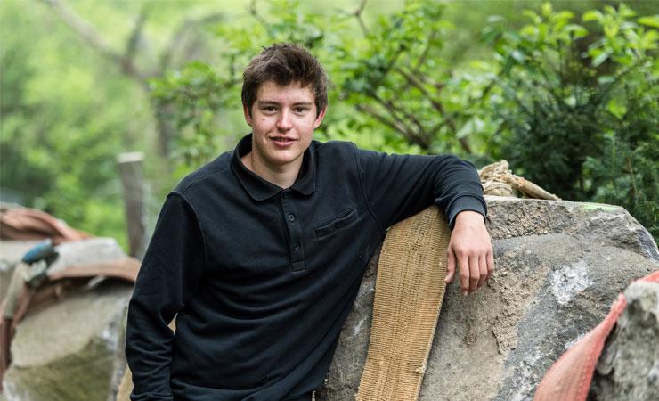 Azubi Marcel Steiner angelehnt an große Natursteine