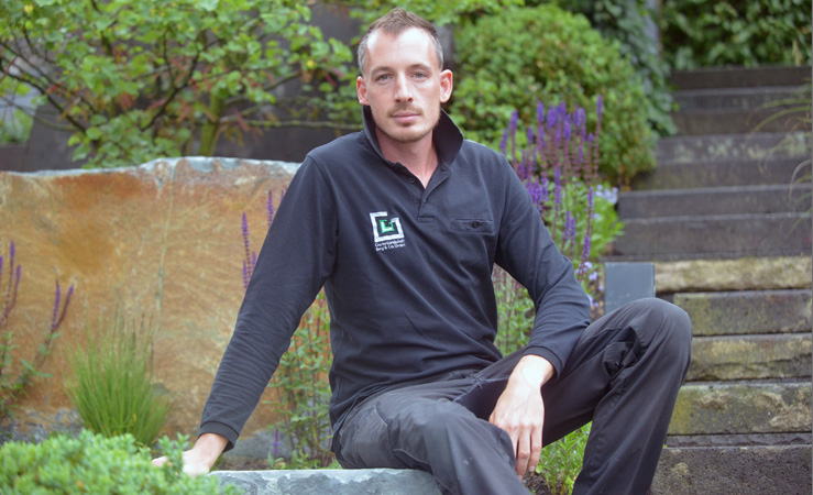 Employee sitting on a natural stone in a garden
