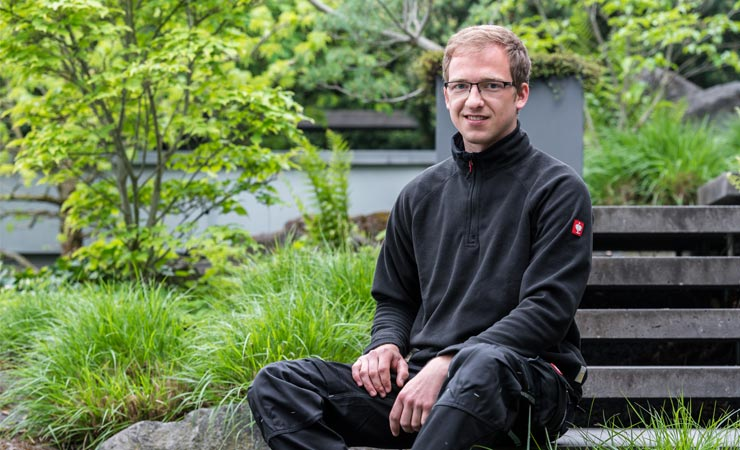 Gärtner Petalla Dietzen in bepflanztem Garten auf Bank