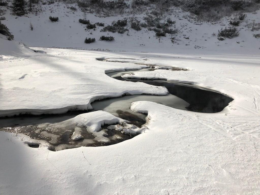 Teilweise zugefrorener Bachlauf in Schneelandschaft