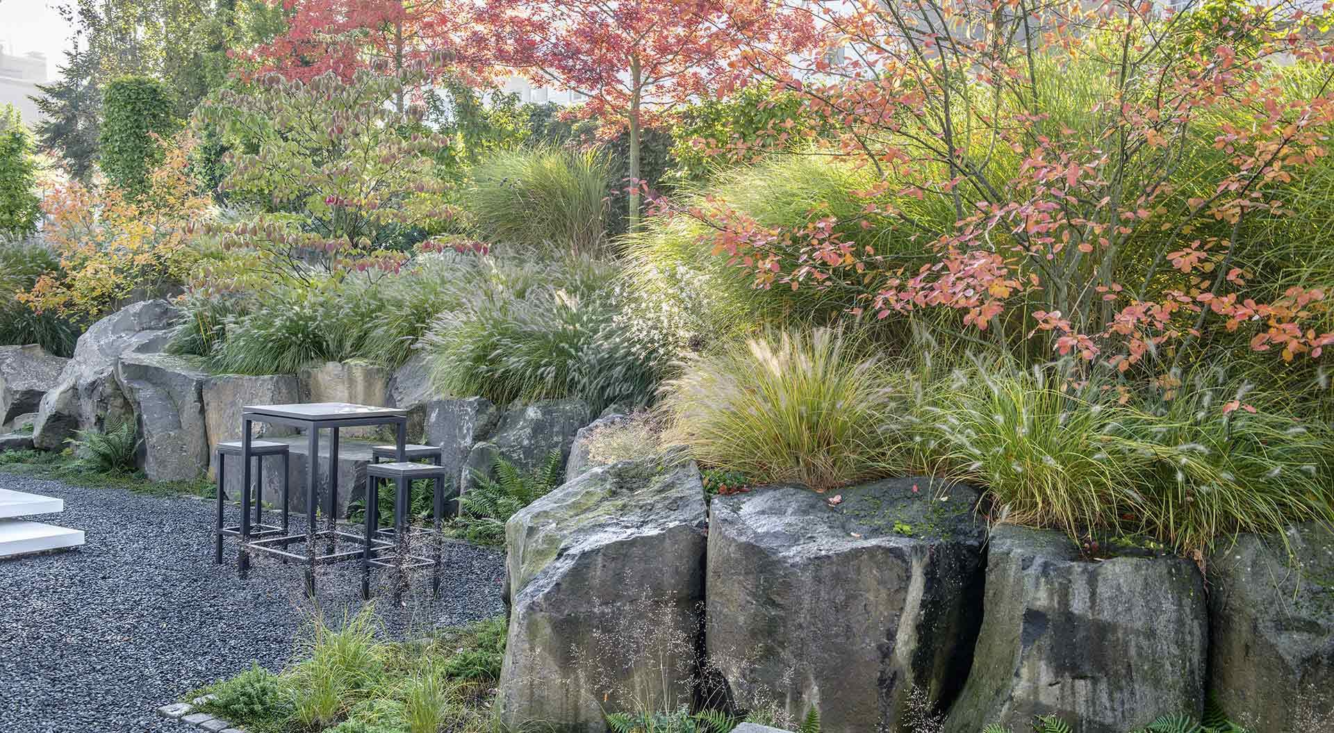 Tisch und Hocker auf Kies-Plateau in mitten eines modernen Hanggartens